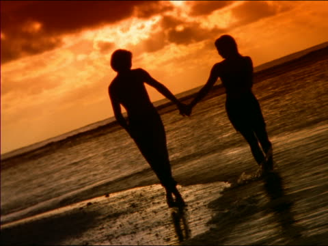 vídeos de stock e filmes b-roll de slow motion canted silhouetted young couple holding hands walking in surf on beach at sunset / seychelles - perto