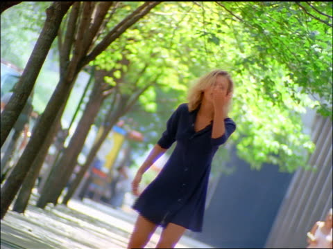 slow motion canted skipping blonde woman blowing kiss at camera as she walks away on nyc street - 1997 stock videos & royalty-free footage