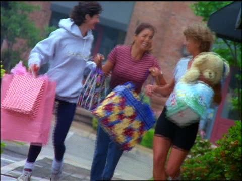 slow motion CANTED three women carrying shopping bags running towards camera + laughing / San Antonio