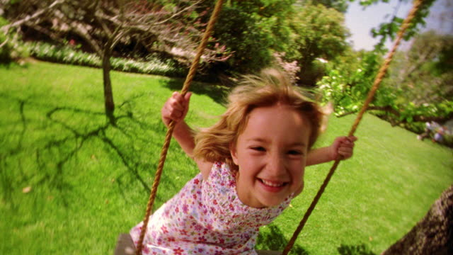 slow motion canted wide shot blonde girl swinging on tree swing toward camera + smiling - 揺れる点の映像素材/bロール