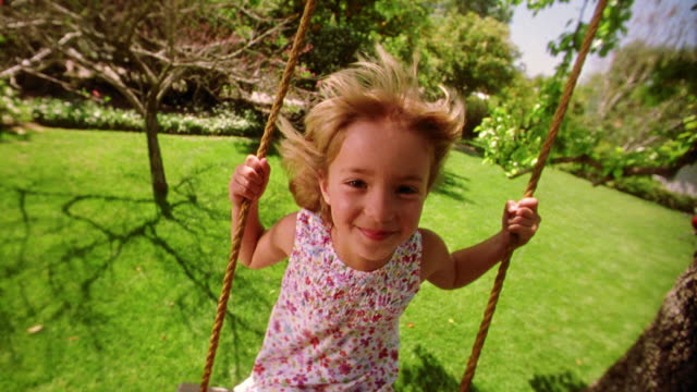 vidéos et rushes de slow motion canted wide shot blonde girl swinging on tree swing toward camera, smiling + sticking out tongue - grimace de pitre