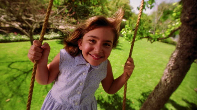 vidéos et rushes de slow motion canted wide shot girl swinging on tree swing toward camera smiling - balançoire