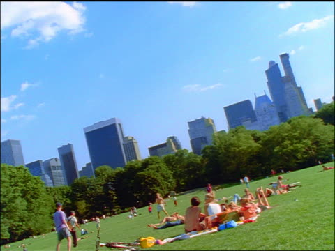 slow motion canted wide shot people in sheeps meadow of central park / manhattan skyline in background - sheep meadow central park stock videos and b-roll footage