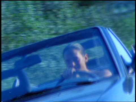 blue slow motion canted pan woman driving convertible on country road / corsica - blue convertible stock videos & royalty-free footage