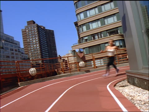 slow motion CANTED woman running around curve of track on roof of building / buildings in background / NYC