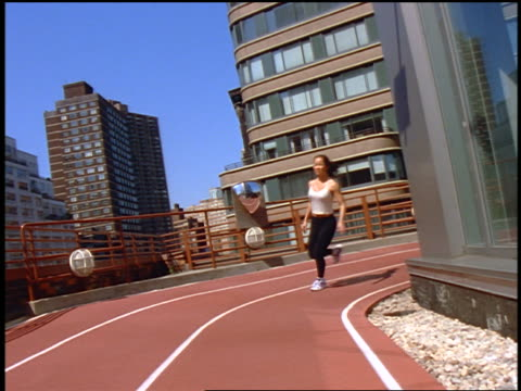 slow motion canted woman running around curve of track on roof of building / buildings in background / nyc - lycra stock-videos und b-roll-filmmaterial