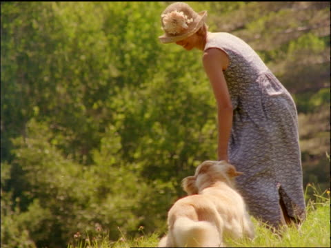 slow motion canted woman wearing sundress + hat walking with dog away from camera outdoors - strohhut stock-videos und b-roll-filmmaterial