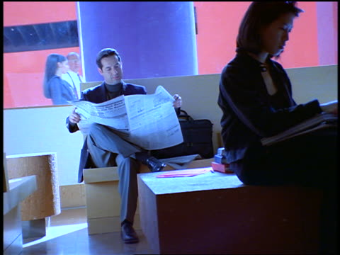 slow motion canted zoom in businessman sitting + reading newspaper in waiting room / he takes calculator out - one mid adult man only stock videos & royalty-free footage