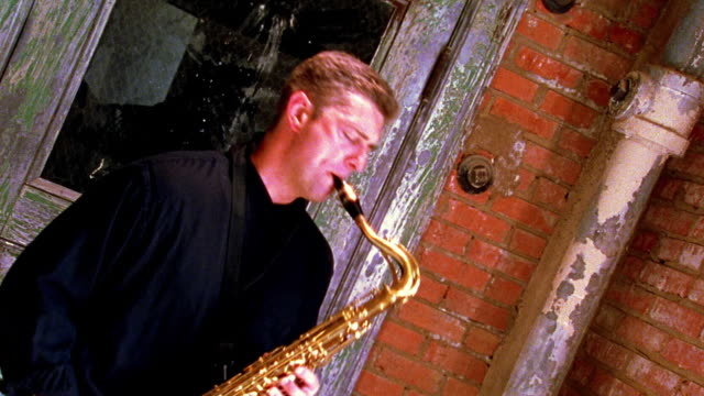 stockvideo's en b-roll-footage met high contrast blurred slow motion canted ms zoom in tilt down man playing saxophone in front of door - saxofonist