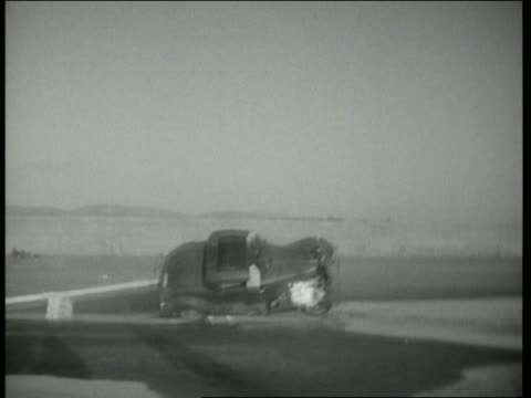 b/w 1943 slow motion car in flames crashing + flipping over in water on ground / hollywood daredevils - acrobazia video stock e b–roll