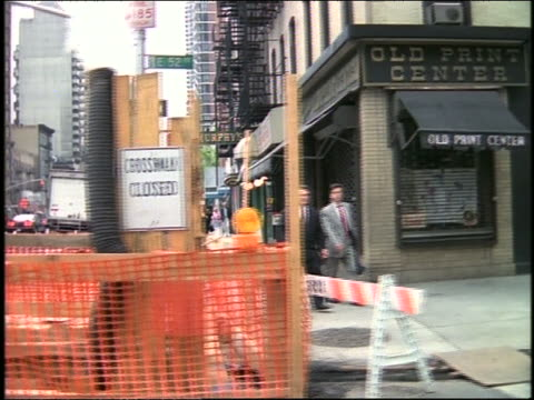 slow motion car point of view of businessmen on sidewalk + construction on nyc street - londonalight stock videos and b-roll footage