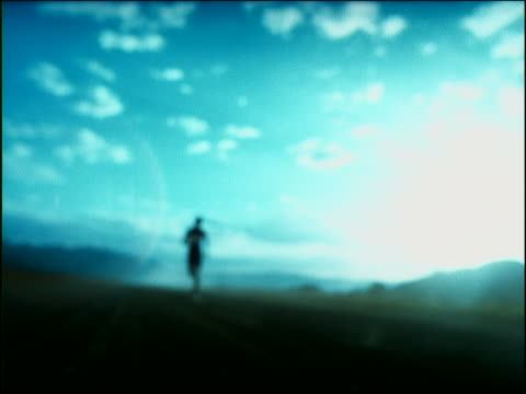slow motion car point of view rack focus toward rear view silhouetted black male athlete running in desert / africa - sheppard132点の映像素材/bロール