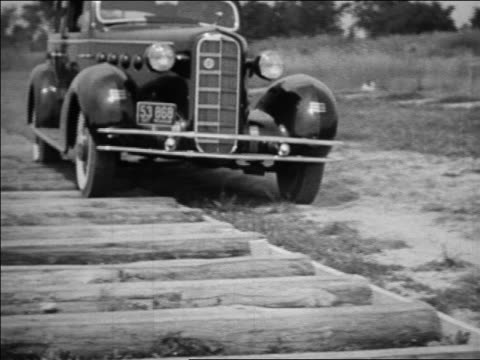 b/w 1934 slow motion car with whitewall tires driving over logs / industrial - 1934 stock-videos und b-roll-filmmaterial