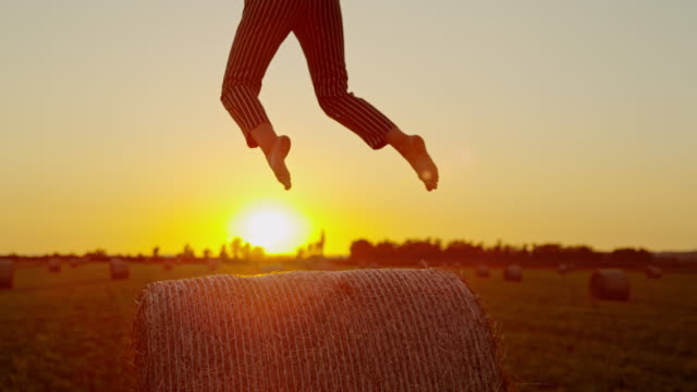 slow motion. ms carefree woman jumping on hay bale in idyllic rural field at sunset - hay field stock videos & royalty-free footage