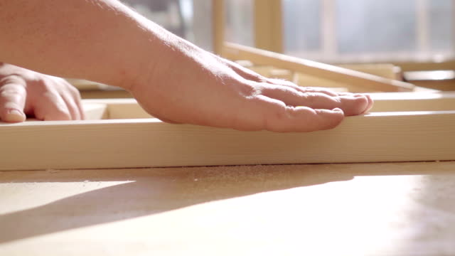 Slow motion: Carpenter sanding wood