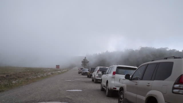 Slow Motion: Cars Parked on Gravel Road in Misty Landscape