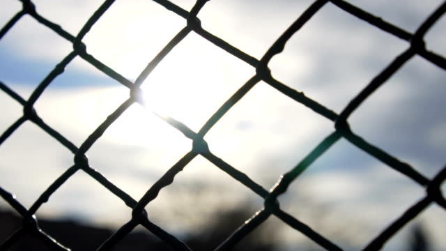 vídeos de stock e filmes b-roll de slow motion: chain fence against golden sun - cerca