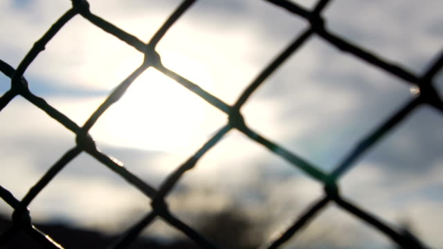 slow motion: chain fence against golden sun - recinzione video stock e b–roll