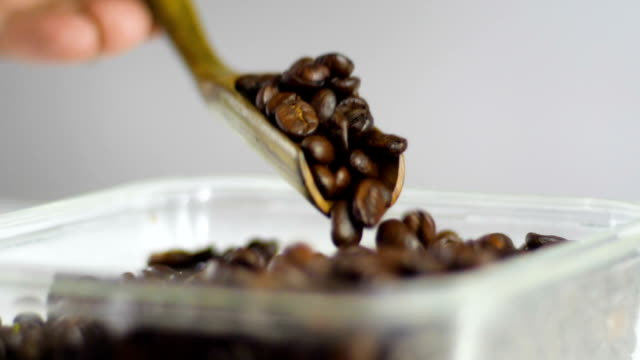 slow motion: checking quality of roasted coffee beans with wooden spoon - cafe macchiato stock videos and b-roll footage