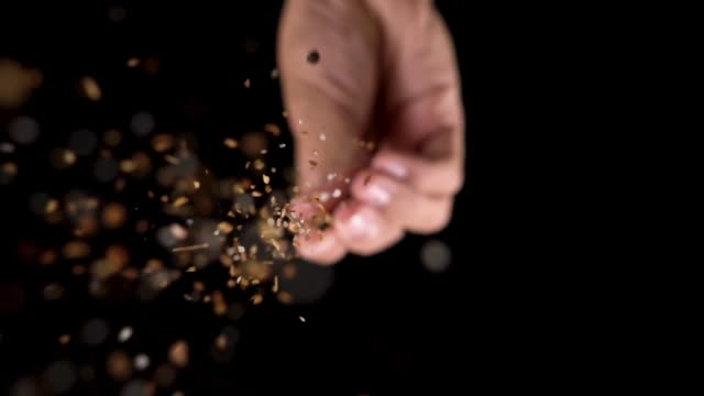 vídeos de stock e filmes b-roll de slow motion: chef hand in and sprinkling seasoning on top of camera. - gastrónomo