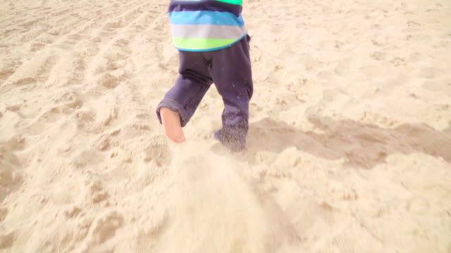 Slow motion: Child foot running on beach
