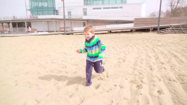 Slow motion: Child running on beach