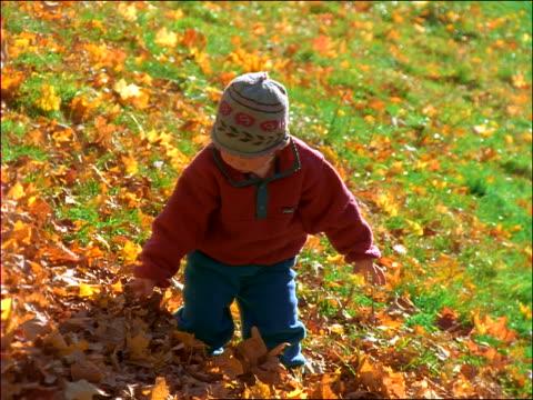 stockvideo's en b-roll-footage met slow motion child smelling autumn leaf - alleen meisjes
