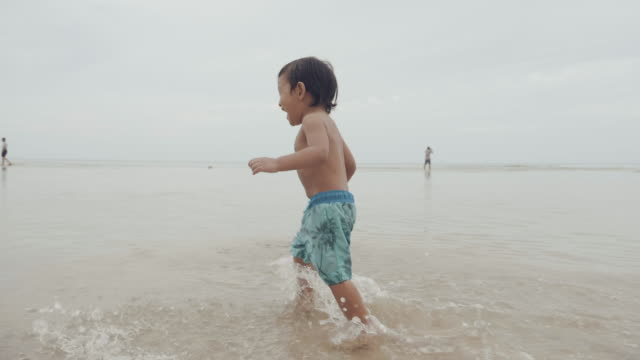 slow motion : child walking on beach - 12 23 months stock videos & royalty-free footage