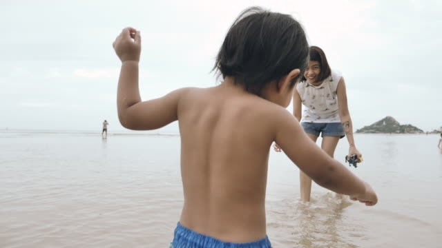 slow motion : child walking to his mother on beach - 12 23 months stock videos & royalty-free footage