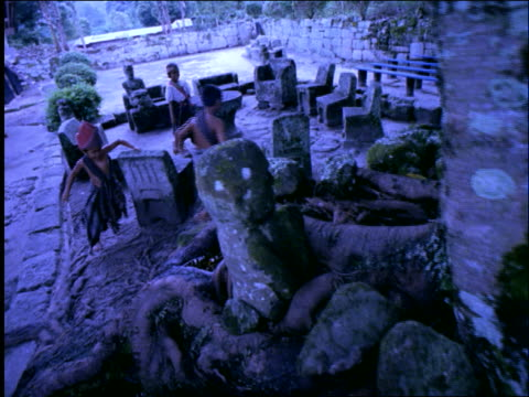 slow motion children running around stone tables + chairs / samosir island on lake toba / sumatra - solo bambini maschi video stock e b–roll