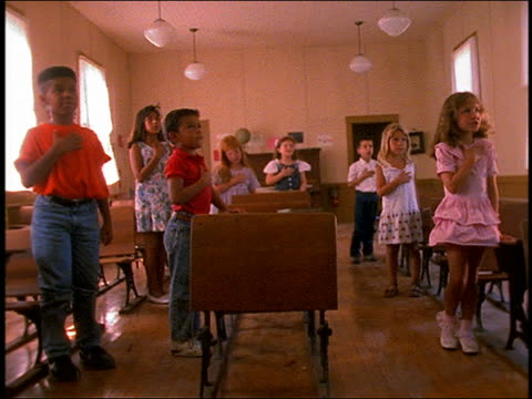 slow motion children say pledge of allegiance and sit / classroom
