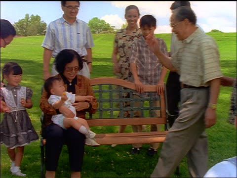 vidéos et rushes de slow motion chinese family joining grandmother with baby on bench to pose for photo outdoors - petit enfant