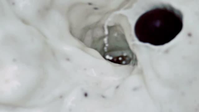 slow motion Chocolate Balls Splashing Into Milk
