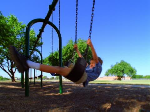 Slow motion clip of a boy swinging.