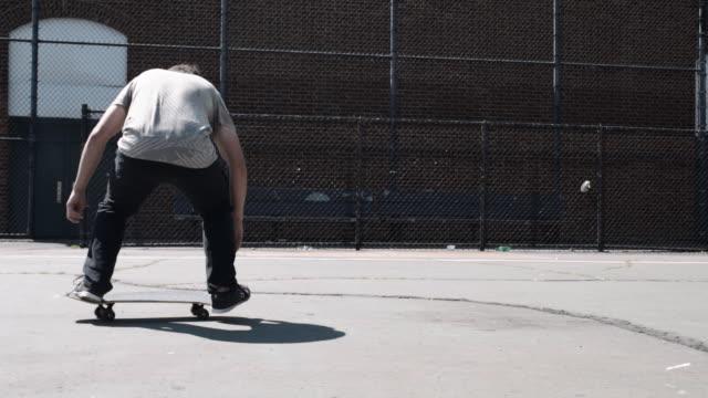 slow motion clip of a freestyle skateboarder at a brooklyn schoolyard - fence点の映像素材/bロール