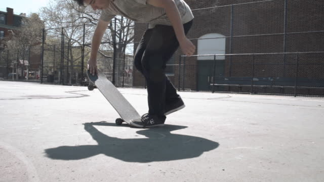 Slow Motion clip of a freestyle skateboarder at a Brooklyn schoolyard