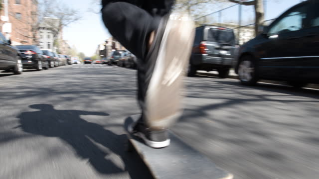 Slow Motion clip of a young, caucasian man skateboarding through the streets of Brooklyn, NYC