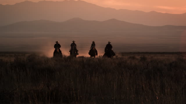 Slow motion clip of cowboys galloping in distance.