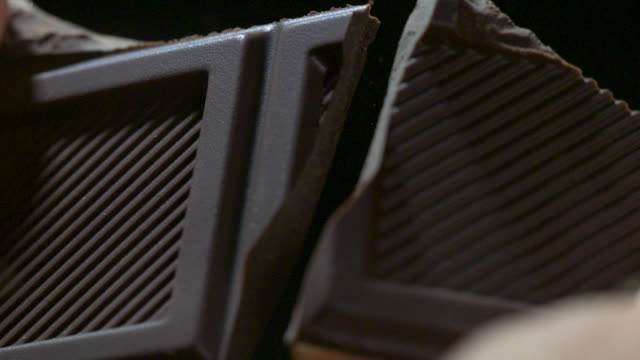 stockvideo's en b-roll-footage met slow motion close shot of a bar of dark chocolate being snapped in half. - bijten
