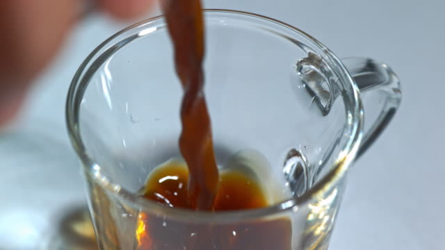 vídeos de stock e filmes b-roll de slow motion close shot of coffee being poured into a glass cup. - copo