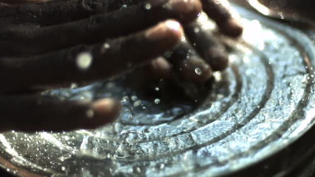 Slow motion close shot of hands splashing water on a tin can.