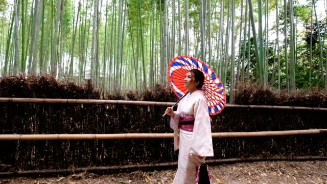 stockvideo's en b-roll-footage met 4k slow motion close-up: een aziatische vrouw draagt kimono jurk wandelen door bamboe bosjes shee en sagano. japanse cultuur - alleen één tienermeisje