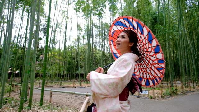 4 k スローモーション クローズ アップ: 竹の木立嵐山・嵯峨野を歩く着物ドレスを着ているアジアの女性。日本の文化 - 扮装点の映像素材/bロール