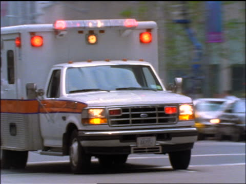 slow motion close up ambulance driving past camera on nyc street - ambulance stock videos & royalty-free footage
