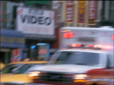 slow motion close up ambulance van driving past camera on NYC street