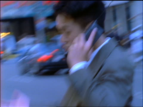 BLUE slow motion close up PAN Asian businessman talking on cellular phone + walking on NYC street