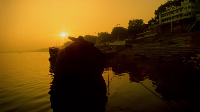 vídeos y material grabado en eventos de stock de slow motion close up boat point of view past moored boat near shore of ganges river at sunset / varanasi, india - imagen virada