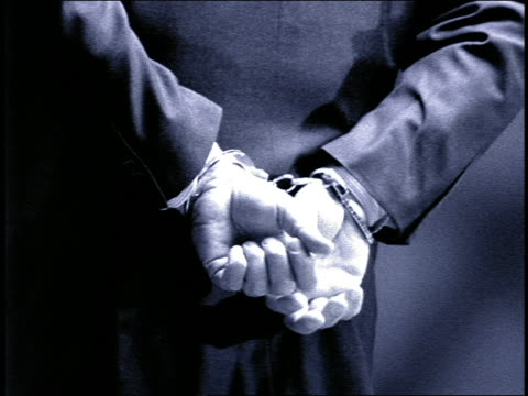 B/W GRAINY slow motion close up businessman with hands handcuffed behind his back