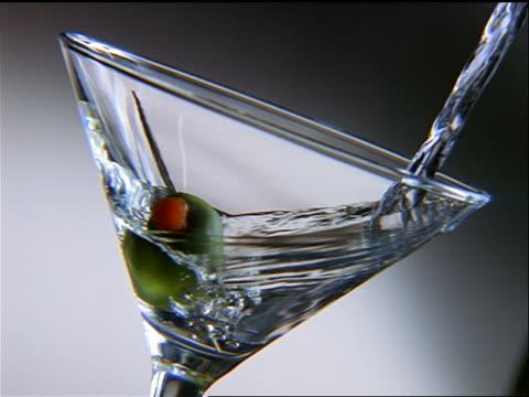 vidéos et rushes de slow motion close up clear liquid being poured into martini glass with olive - un seul objet