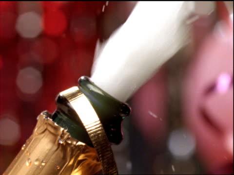 slow motion close up cork explodes from champagne bottle / streamers in background - sektkorken stock-videos und b-roll-filmmaterial